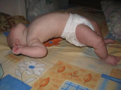 Грудничок выгибается и запрокидывает голову назад во сне: причины, не вредно ли это?