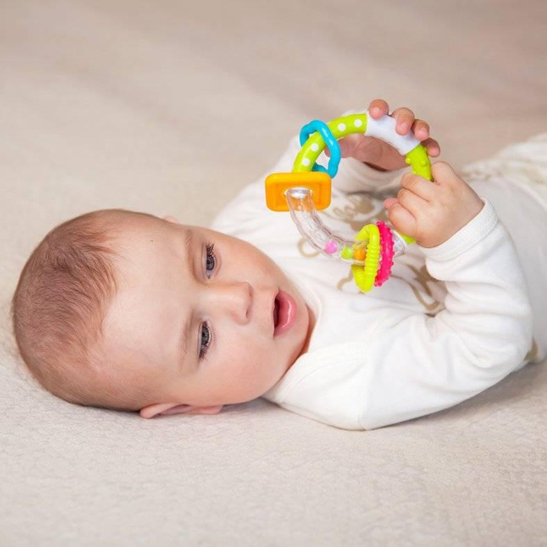 Погремушки для новорожденных на кроватку и в коляску: во сколько месяцев ребенок начинает их держать
